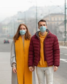 Vista frontale delle coppie che propongono insieme alle maschere mediche