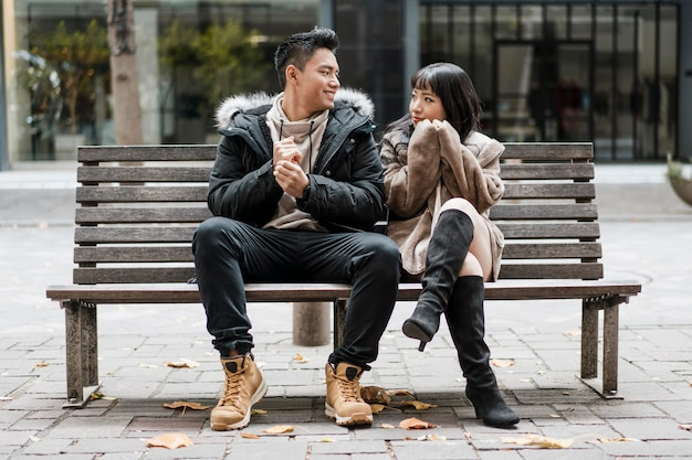 Front view of couple sitting on a bench together