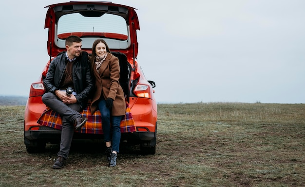 Front view of couple sitting in the car's trunk with copy space