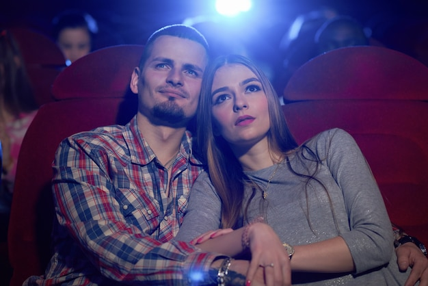 Front view of couple sitting together in cinema, watching comedy or romantic movie. handsome bearded man hugging beautiful girlfriend sitting near while movie review. concept of leisure.