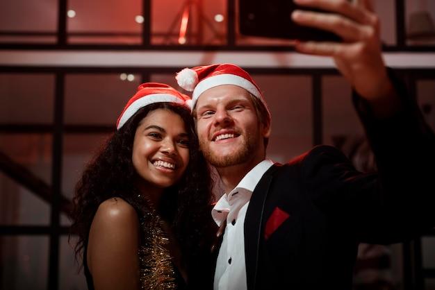 Пара вид спереди, делающая селфи на вечеринке в канун нового года