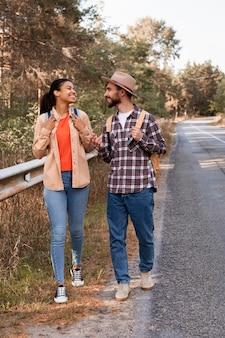 Пара вид спереди гуляет по обочине дороги