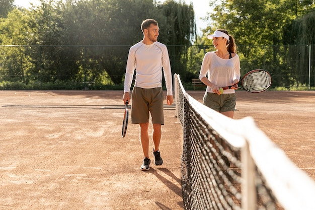 Front view couple on tennis court