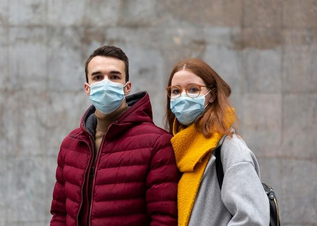 Vista frontale delle coppie che indossano maschere mediche insieme