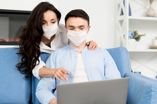 Front view of couple with face masks at home on laptop
