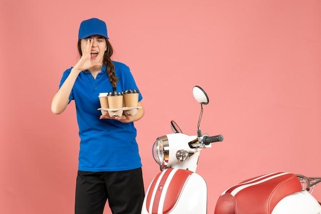 Vista frontale della ragazza del corriere in piedi accanto alla moto con in mano il caffè che chiama qualcuno su uno sfondo color pesca pastello