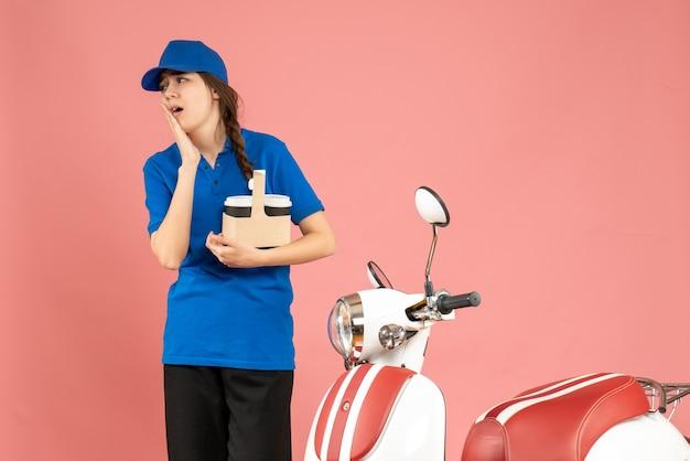 Vista frontale della ragazza del corriere in piedi accanto alla moto che tiene il caffè spaventata su uno sfondo color pesca pastello