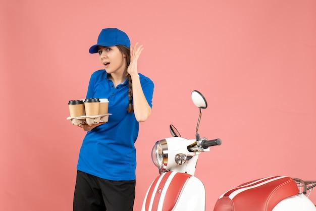 Vista frontale della ragazza del corriere in piedi accanto alla moto con in mano caffè e piccole torte ascoltando l'ultimo spettegolare su uno sfondo color pesca pastello