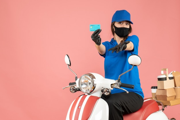 Front view of courier girl wearing medical mask and gloves sitting on scooter holding bank card delivering orders on pastel peach background
