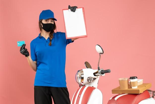 Vista frontale della ragazza del corriere che indossa guanti con maschera medica in piedi accanto alla motocicletta con una torta di caffè su di essa che tiene documenti carta di credito su sfondo color pesca pastello