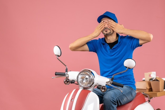 Front view of courier guy wearing hat sitting on scooter closing his eyes on pastel peach background