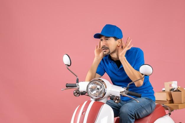 Vista frontale del ragazzo del corriere che indossa un cappello seduto su uno scooter ascoltando l'ultimo spettegolare su sfondo color pesca pastello