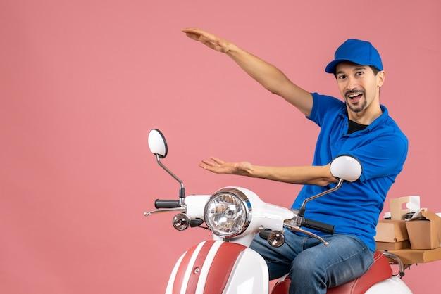 Vista frontale del ragazzo del corriere che indossa un cappello seduto su uno scooter che fa qualcosa di preciso su uno sfondo color pesca pastello
