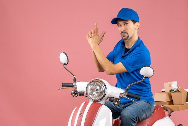 Front view of courier guy wearing hat sitting on scooter and making gun gesture on pastel peach background