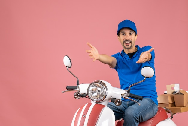 Front view of courier guy wearing hat sitting on scooter receiving something on pastel peach background