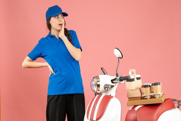 Vista frontale della signora del corriere in piedi accanto alla moto con caffè e piccole torte su di essa sentirsi confusa su uno sfondo color pesca pastello