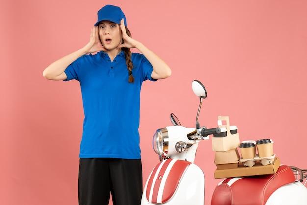 Vista frontale della signora del corriere in piedi accanto alla motocicletta con caffè e piccole torte su di essa sentendosi sorpresa sullo sfondo color pesca pastello