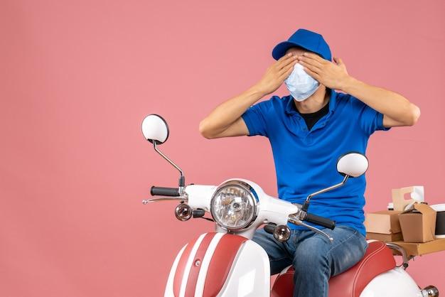 Vista frontale del corriere in maschera medica che indossa un cappello seduto su uno scooter chiudendo gli occhi su sfondo color pesca pastello