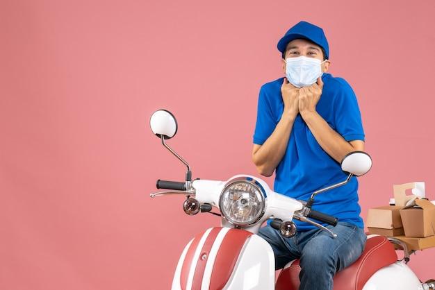 Vista frontale dell'uomo corriere in maschera medica che indossa cappello seduto su scooter e guardando qualcosa con espressione facciale sorridente su sfondo pesca pastello