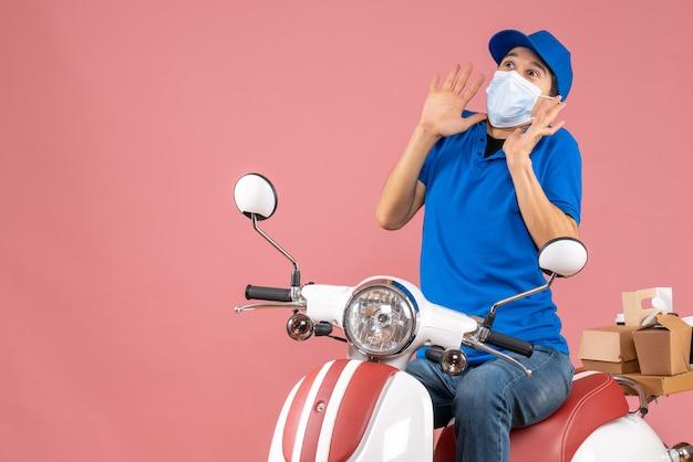 Vista frontale dell'uomo corriere in maschera medica che indossa cappello seduto su scooter e alzando lo sguardo con espressione facciale spaventata su sfondo pesca pastello