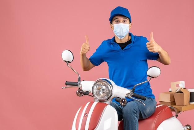 Vista frontale dell'uomo corriere in maschera medica che indossa un cappello seduto su uno scooter che fa un gesto ok su sfondo color pesca pastello pastel