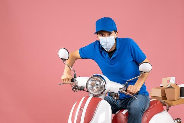 Vista frontale dell'uomo corriere in maschera medica che indossa cappello seduto su scooter su sfondo pesca pastello
