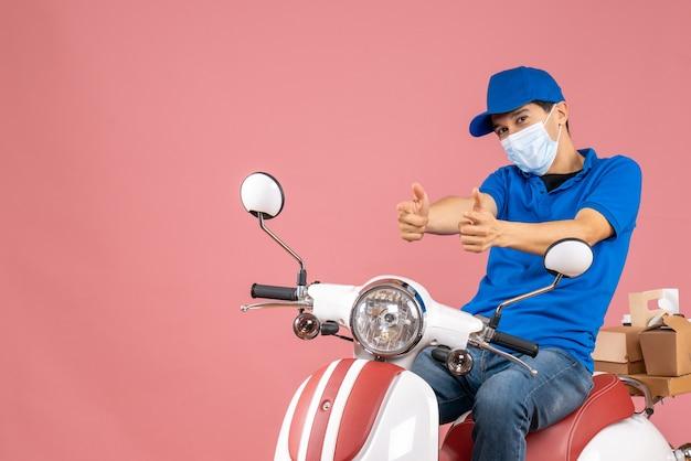 Vista frontale dell'uomo corriere in maschera medica che indossa un cappello seduto su uno scooter e che punta in avanti su sfondo color pesca pastello