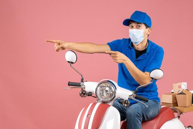 Vista frontale del corriere in maschera medica che indossa un cappello seduto su uno scooter e indica qualcosa sul lato destro su sfondo color pesca pastello