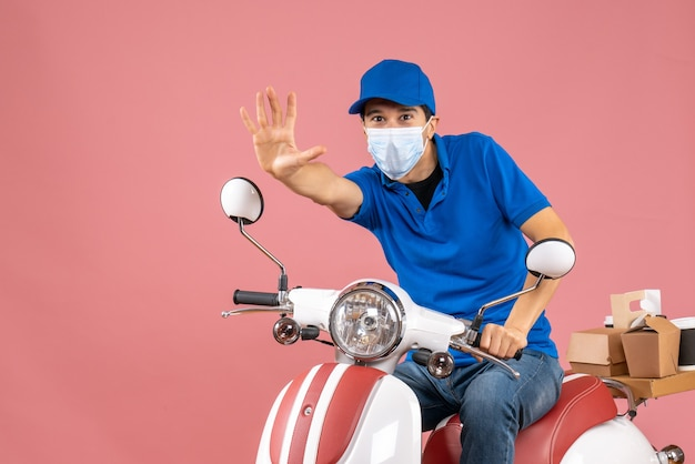 Vista frontale dell'uomo corriere in maschera medica che indossa un cappello seduto su uno scooter che mostra cinque su sfondo color pesca pastello