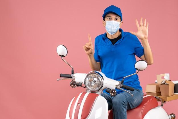 Vista frontale dell'uomo corriere in maschera medica che indossa un cappello seduto su uno scooter che mostra cinque che puntano verso l'alto su sfondo color pesca pastello