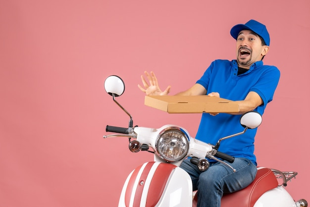Front view of courier man wearing hat sitting on scooter feeling anxious on pastel peach background