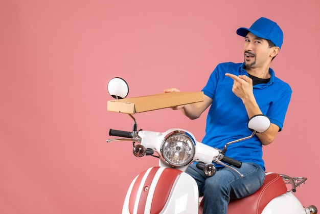 Front view of courier man wearing hat sitting on scooter feeling confident on pastel peach background