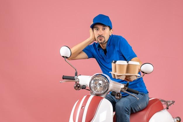 Vista frontale dell'uomo corriere che indossa un cappello seduto sullo scooter sentendosi scioccato sullo sfondo color pesca pastello