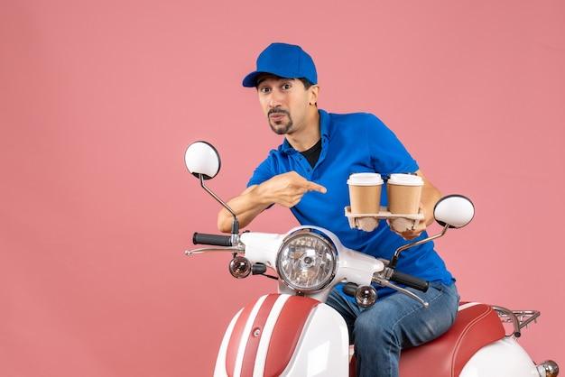 Vista frontale dell'uomo corriere che indossa un cappello seduto su uno scooter che non si sente sicuro sullo sfondo color pesca pastello