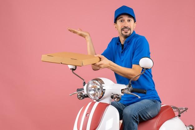 Vista frontale del corriere che indossa un cappello seduto su uno scooter che tiene l'ordine e fa qualcosa di preciso su uno sfondo color pesca pastello