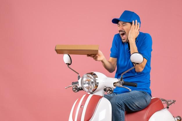 Vista frontale del corriere che indossa un cappello seduto su uno scooter che soffre di mal di testa su sfondo color pesca pastello