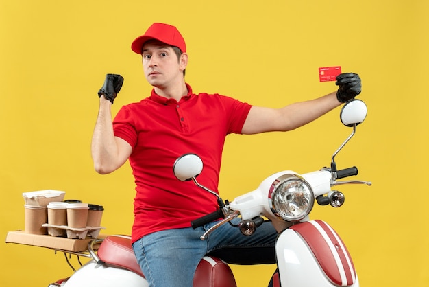 Vista frontale del corriere uomo che indossa camicetta rossa e guanti cappello in maschera medica consegna ordine seduto su scooter che indica carta bancaria che mostra indietro