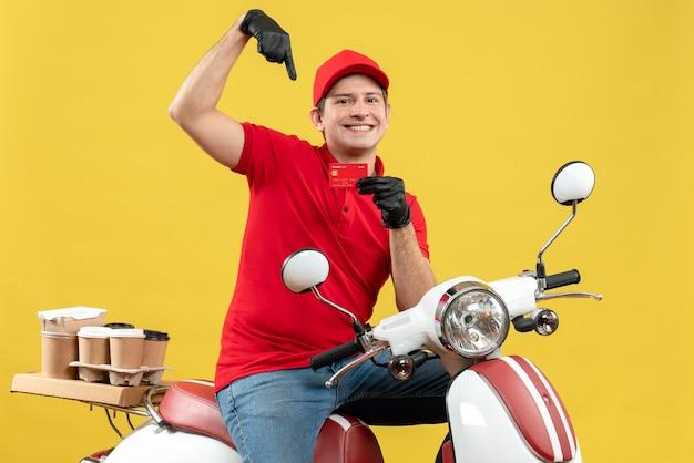 Vista frontale del corriere uomo che indossa camicia rossa e guanti cappello nella mascherina medica che trasporta ordine seduto su uno scooter che punta la carta di credito