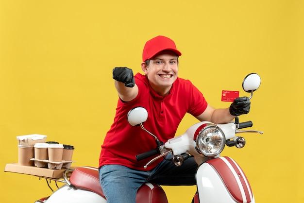 Vista frontale del corriere uomo che indossa camicetta rossa e guanti cappello in maschera medica consegna ordine seduto su scooter che mostra la carta di credito