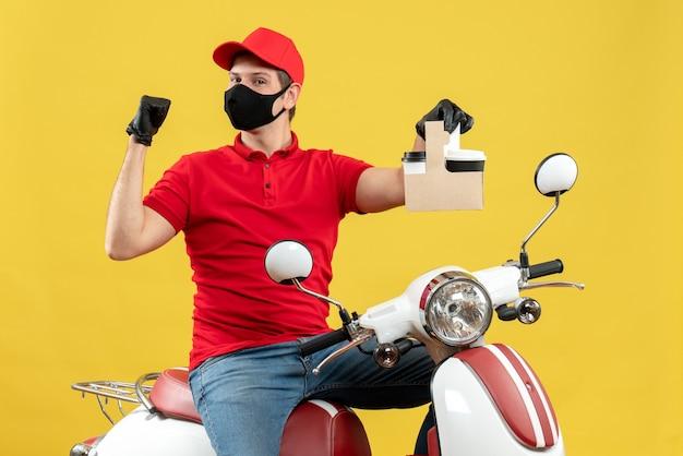 Vista frontale del corriere uomo che indossa camicetta rossa e guanti cappello in mascherina medica che si siede sullo scooter tenendo gli ordini sentirsi orgogliosi