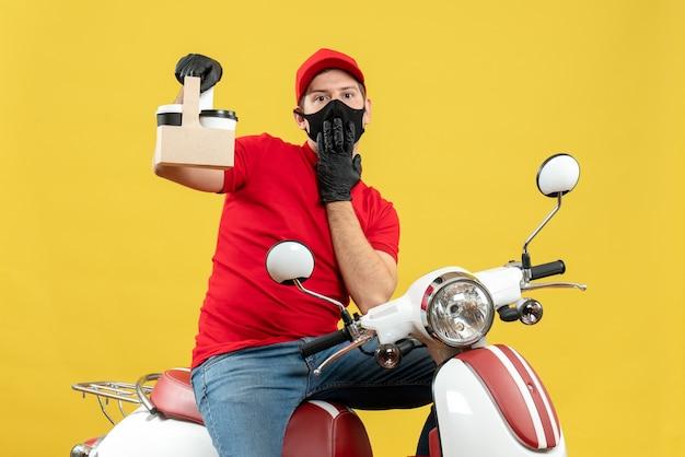 Vista frontale del corriere uomo che indossa camicetta rossa e guanti cappello in mascherina medica seduto su scooter tenendo gli ordini sentirsi sorpreso