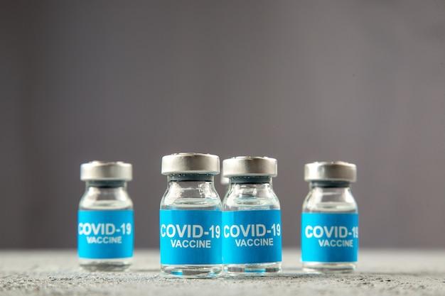 Vista frontale dei vaccini covid in piedi fianco a fianco su sfondo grigio onda con spazio libero