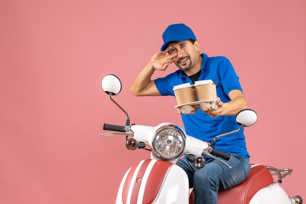 Front view of crazy emotional funny courier man wearing hat sitting on scooter on pastel peach background