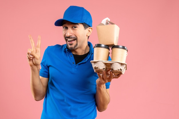 Front view of crazy emotional male delivery guy wearing hat holding orders making victory gesture