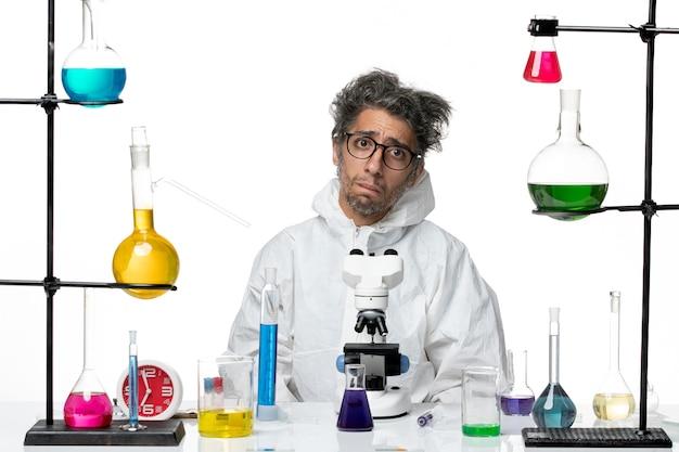 Вид спереди сумасшедший ученый-мужчина в специальном защитном костюме, сидящий за столом с растворами на светло-белом фоне, вирус науки лаборатории covid