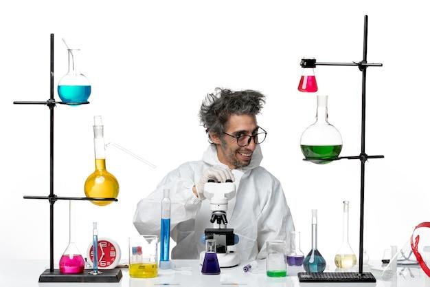 白い背景の実験室の病気covid科学ウイルスの解決策とテーブルの周りに座っている特別な防護服の正面図狂気の男性科学者