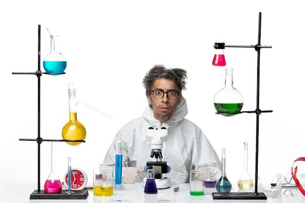 Вид спереди сумасшедший ученый-мужчина в специальном защитном костюме, сидящий за столом с растворами на белом фоне, вирус лабораторной болезни covid science