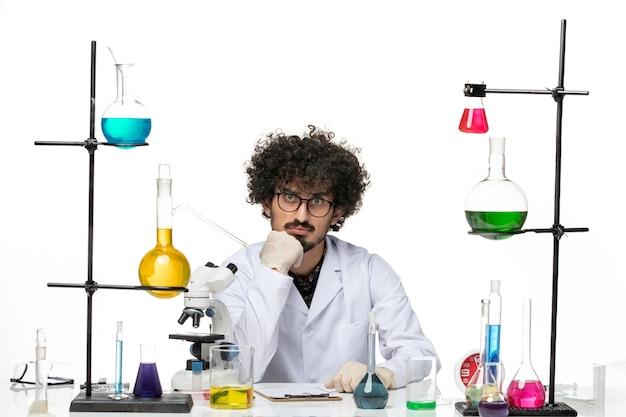 Scienziato maschio pazzo di vista frontale in vestito medico seduto e guardando con attenzione su uno spazio bianco