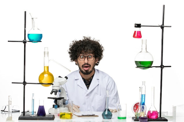 Scienziato maschio pazzo vista frontale in tuta medica seduto e facendo facce buffe su uno spazio bianco