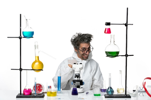 Scienziato maschio pazzo vista frontale in tuta protettiva speciale seduto intorno al tavolo con soluzioni che ride su sfondo bianco virus scienza covid malattia di laboratorio